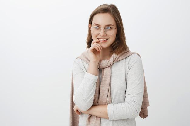 Meisje kijkt nieuwsgierig man probeert aandacht bijtende vinger te draaien en glimlachend geïntrigeerd starend naar links met interesse en verlangen met mysterieus heerlijk idee staande over grijze muur Gratis Foto
