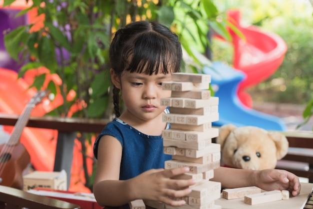 Meisje kind jenga-spellen spelen Premium Foto