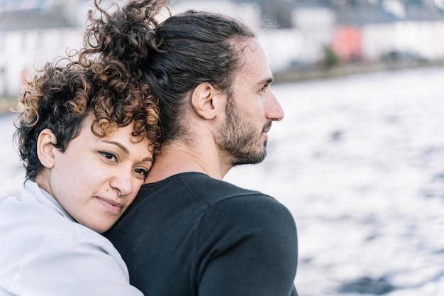 Meisje knuffelen haar partner terug met de zee onscherp Gratis Foto