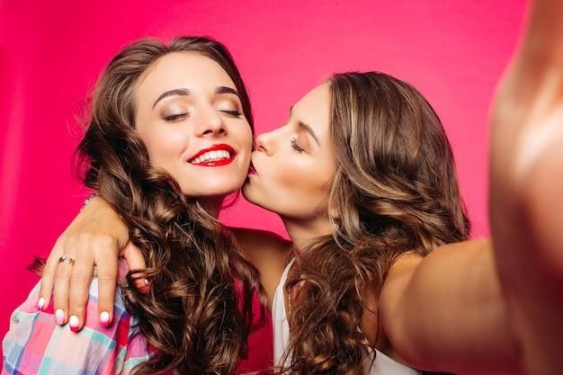 Meisje kuste haar vriend terwijl het maken van selfie. Premium Foto