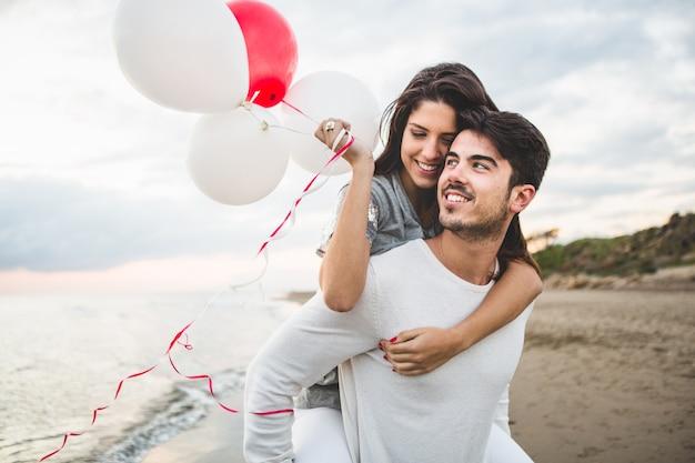 Meisje lacht met ballonnen, terwijl haar vriendje haar draagt op haar rug Gratis Foto