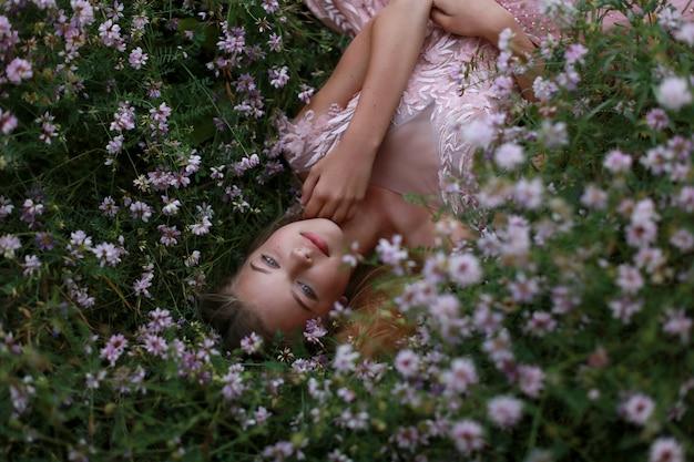 Meisje ligt in bloeiend gras Premium Foto