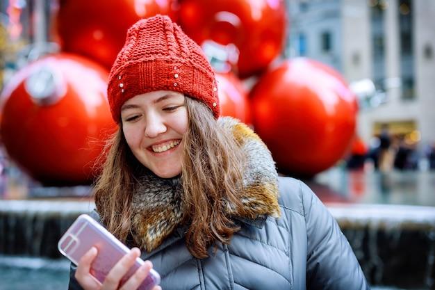 Meisje lopen en sms'en op smartphone in de straat met een rode hoed Premium Foto
