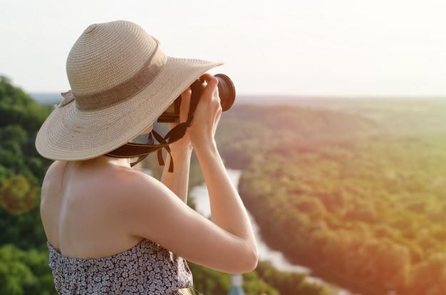 Meisje maakt foto's tegen het bos en de rivier Premium Foto