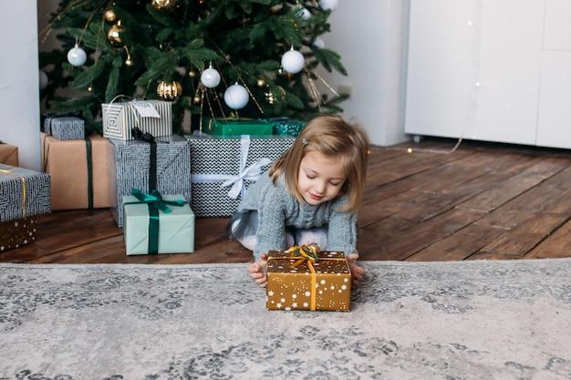 Meisje met aanwezige kerstmis, kerstboom Premium Foto