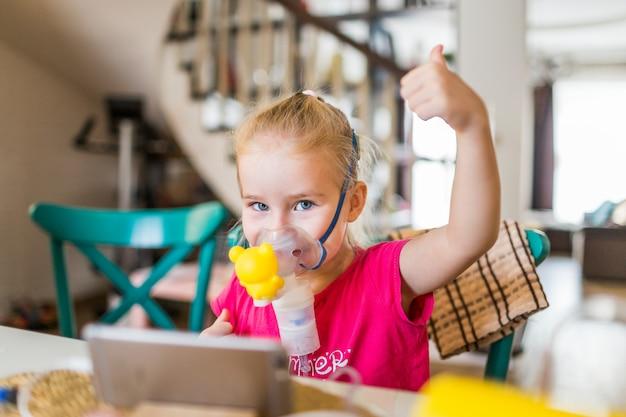 Meisje met allergisch astma gebruikend inhalator en tonend ok. Premium Foto