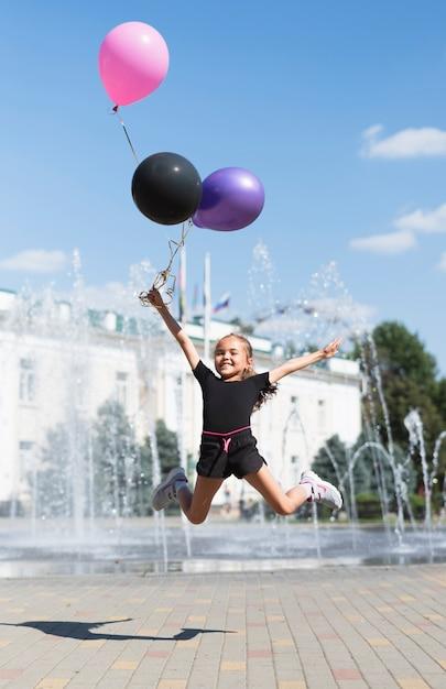 Meisje met ballonnen bij fontein Gratis Foto