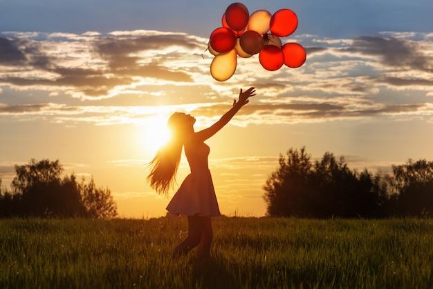 Meisje met ballonnen bij zonsondergang Premium Foto
