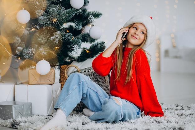 Meisje met behulp van telefoon door kerstboom op kerstmis Gratis Foto