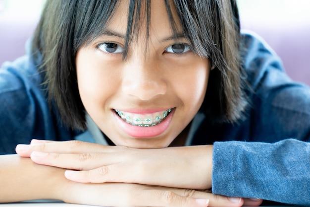 Meisje met beugels tanden glimlachen en gelukkig Premium Foto
