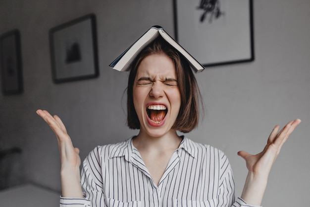 Meisje met boek op haar hoofd schreeuwt heftig. portret van emotionele donkerharige vrouw in witte blouse in kantoor. Gratis Foto