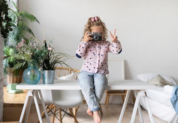 Meisje met camera die vredessymbool toont Gratis Foto