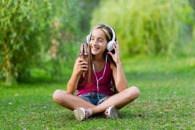 Meisje met chocoladeroomijs en hoofdtelefoons Gratis Foto