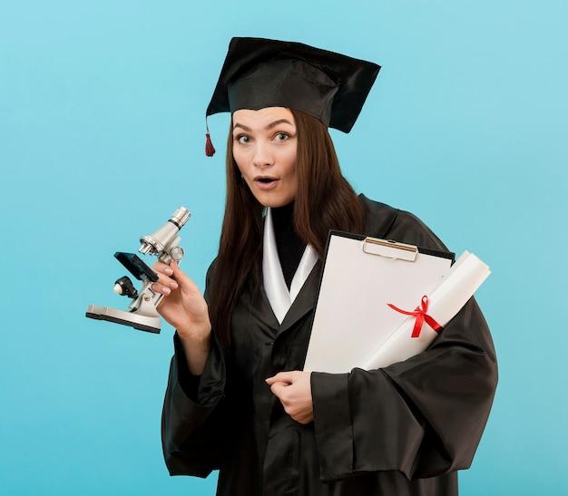 Meisje met diploma en microscoop Gratis Foto