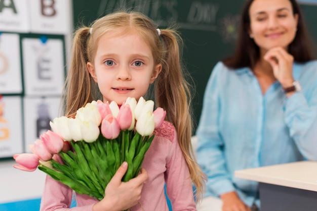 Meisje met een boeket bloemen voor haar leraar Gratis Foto