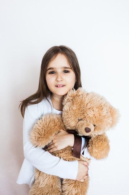 Meisje met een favoriete teddybeer, jeugd en zorg, familie en vrienden. meisje speelt en knuffelen speelgoed Premium Foto
