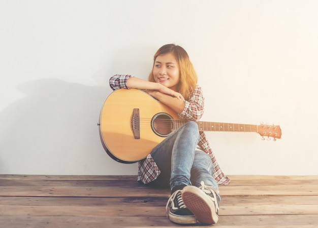 Meisje met een guitarr zittend op de vloer Gratis Foto