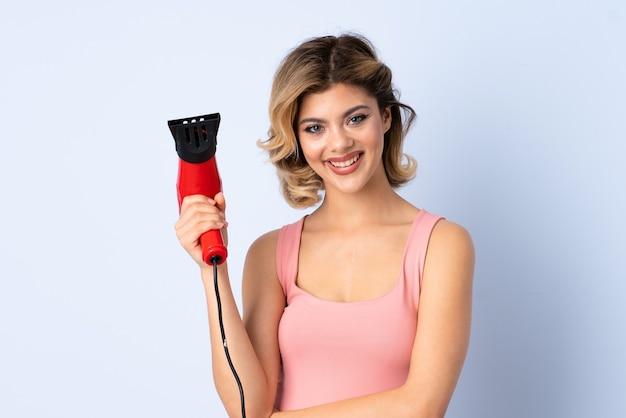 Meisje met een haardroger geïsoleerd op blauw Premium Foto