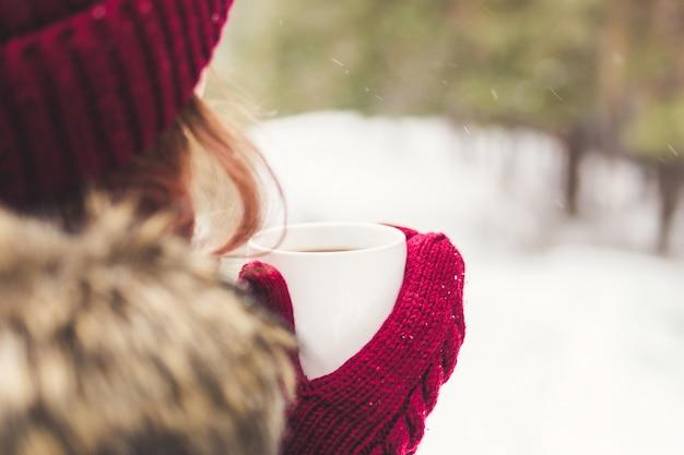 Meisje met een koffiemok in rode wanten in het bos Premium Foto