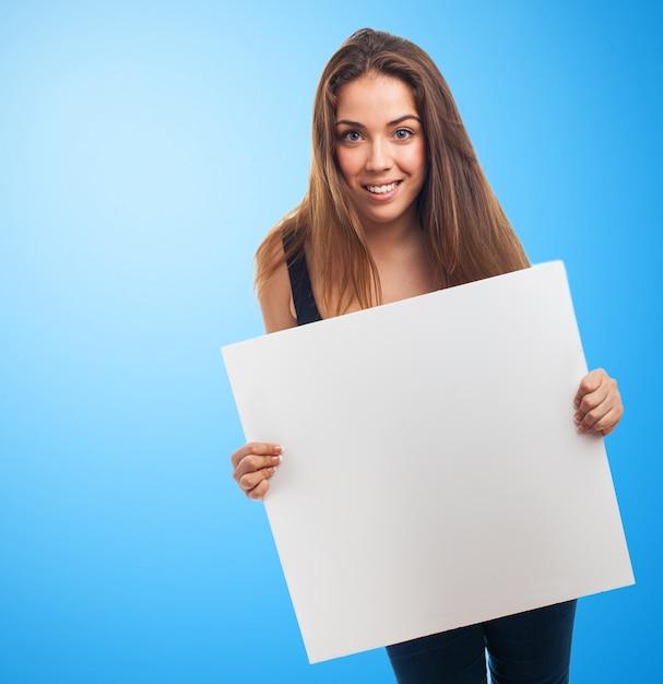 Meisje met een poster in een blauwe achtergrond Gratis Foto