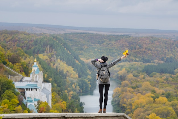 Meisje met een rugzak en een hoed die zich op een heuvel bevindt. handen omhoog. rivier en tempel hieronder. Premium Foto