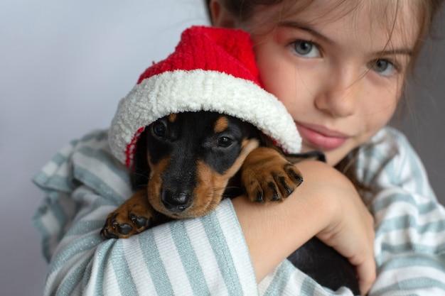 Meisje met een teckel puppy in haar kerstmuts huisdier nieuwjaar cadeau Premium Foto