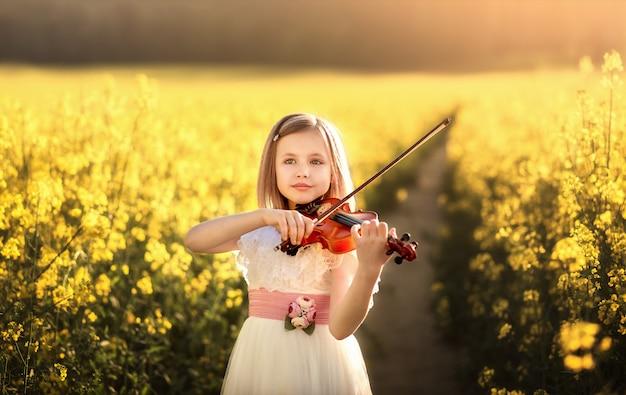 Meisje met een viool in een veld in de zomer Premium Foto