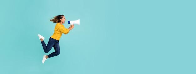 Meisje met en megafoon die springt schreeuwt Premium Foto