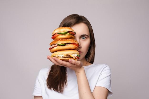 Meisje met enorme hamburger bij de hand. studio portret van jonge brunette vrouw in wit t-shirt met enorme hamburgers aan haar hand op zoek geschokt of verrast Premium Foto