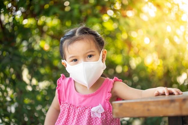 Meisje met gezondheidsmasker beschermt het coronavirus. Premium Foto