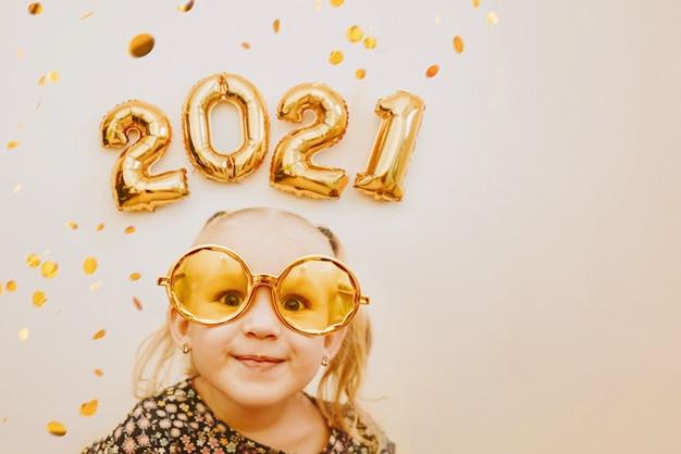 Meisje met gouden maskerade bril glimlachen, gek rond. gelukkig 2021 Premium Foto