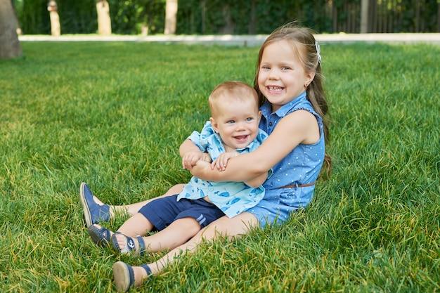 Meisje met haar broer in een park op het gras Premium Foto