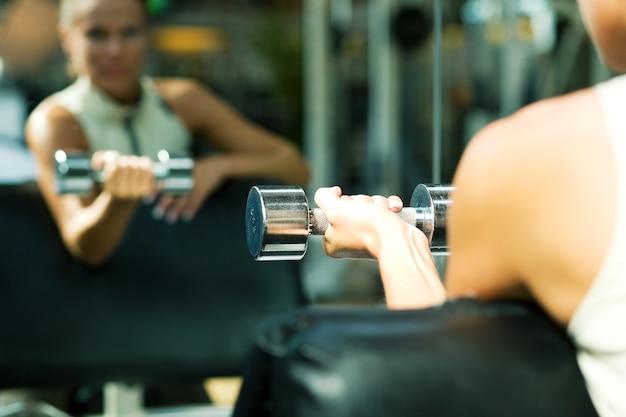 Meisje met halters weerspiegelen in de spiegel Premium Foto