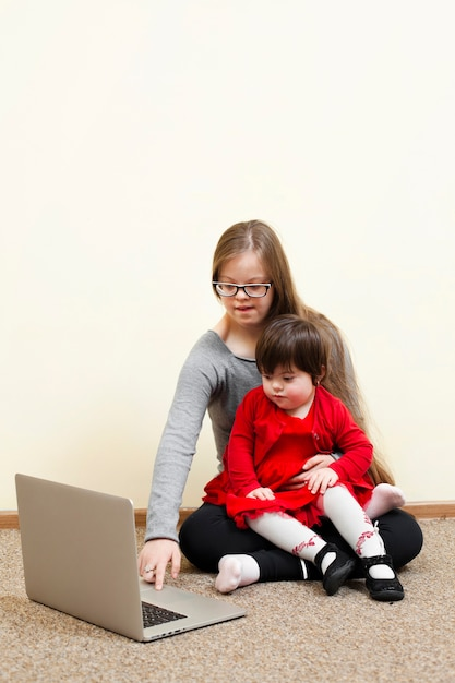 Meisje met het kind van de syndroom van down houden tijdens het kijken naar laptop Gratis Foto