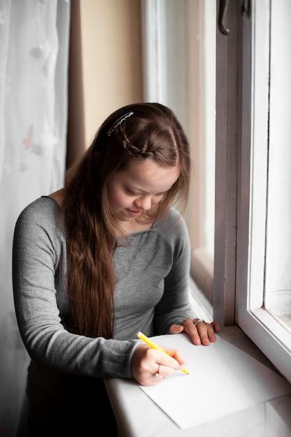Meisje met het syndroom van down bij het raam Gratis Foto
