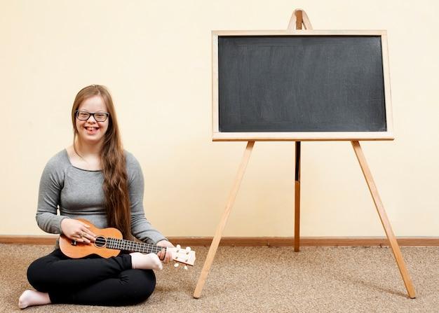 Meisje met het syndroom van down poseren met gitaar en schoolbord Premium Foto