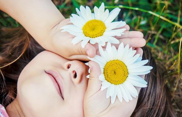 Meisje met kamille. selectieve aandacht. natuur bloemen. Premium Foto