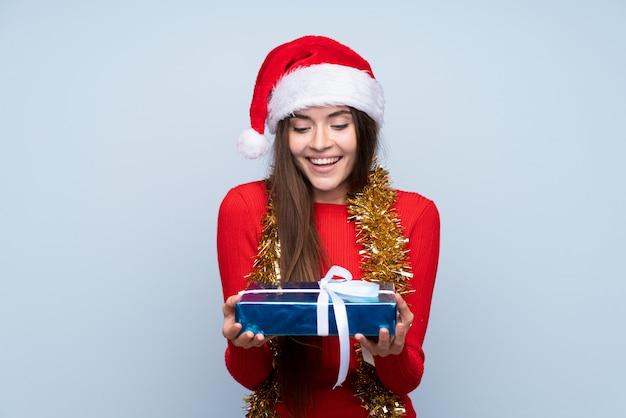 Meisje met kerstmishoed en holding een gift over geïsoleerd blauw Premium Foto