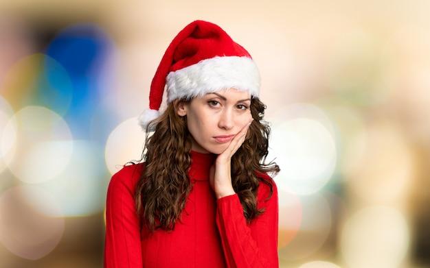 Meisje met kerstmishoed ongelukkig en gefrustreerd over ongericht muur Premium Foto