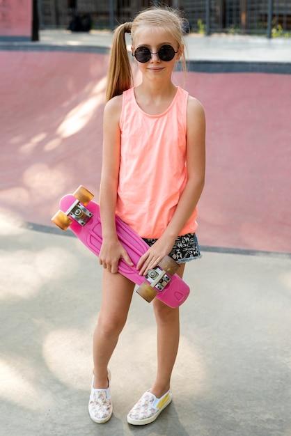 Meisje met korte broek en roze skateboard Gratis Foto