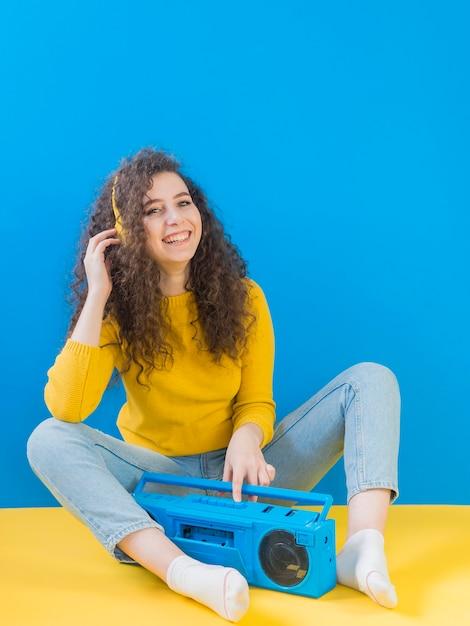 Meisje met krullend haar glimlacht en luistert naar muziek Gratis Foto