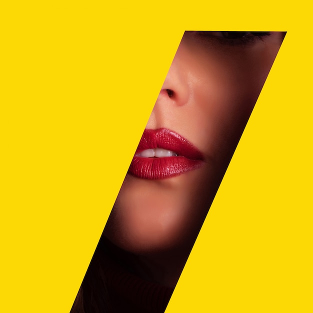 Meisje met lichte make-up door gat in geel papier Premium Foto
