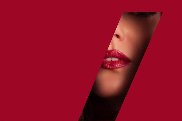 Meisje met lichte make-up, rode lippenstift kijkt door gat in papier Premium Foto
