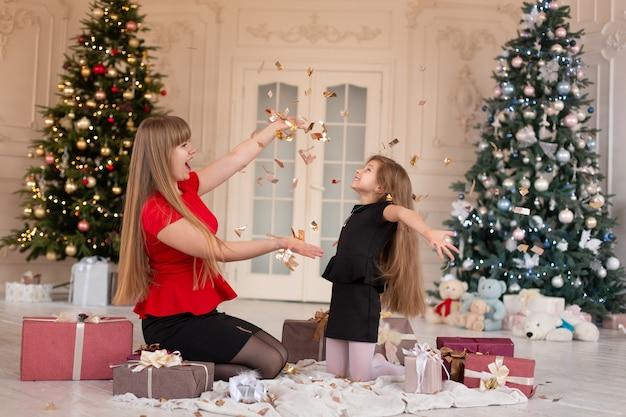 Meisje met maa gooit confetti en opent cadeautjes. kerstmagie. vrolijke momenten van een gelukkige jeugd. Premium Foto