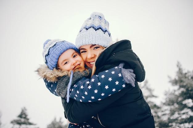 Meisje met moeder het spelen in een de winterpark Gratis Foto