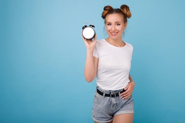 Meisje met onechte wekker op een blauwe ruimte Premium Foto