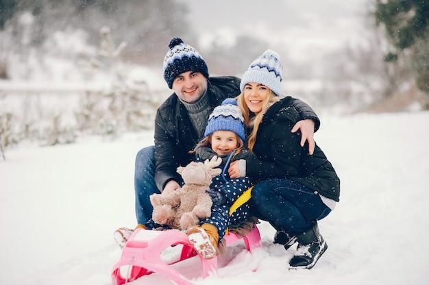 Meisje met ouders die in een de winterpark spelen Gratis Foto