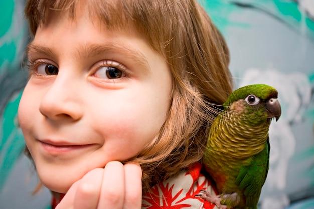 Meisje met papegaai, portret Premium Foto