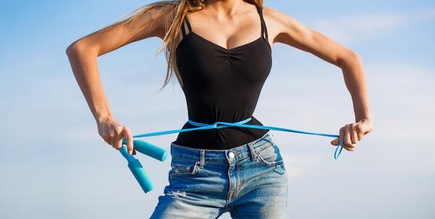 Meisje met perfecte taille met een springtouw in handen. geschikt geschiktheidsmeisje dat haar taille met maatregelenband meet. Premium Foto