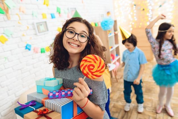 Meisje met presenteert houdt gekleurde lolly in de hand. Premium Foto
